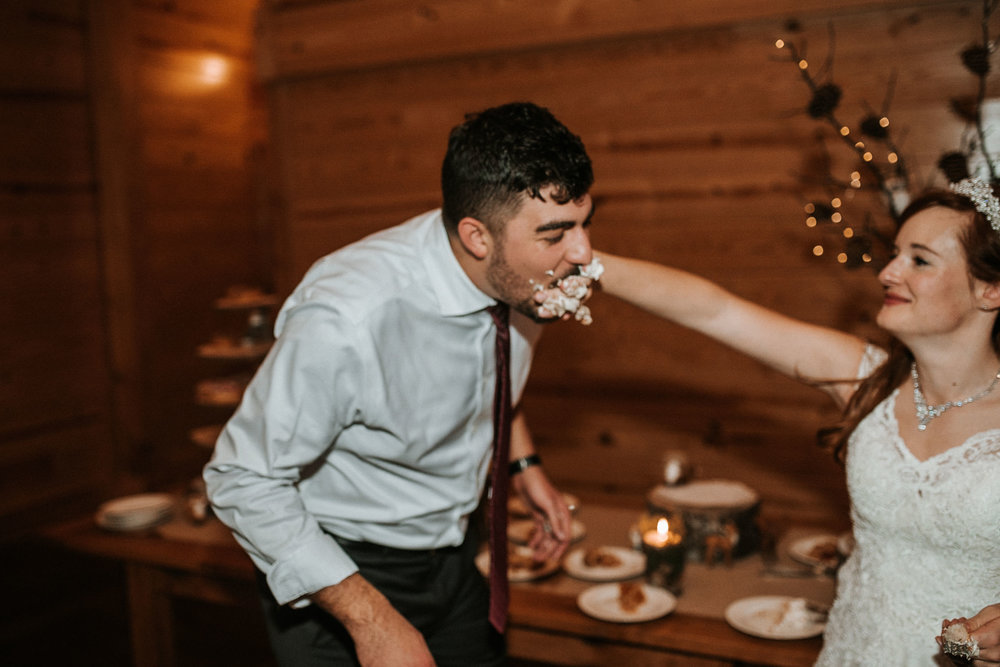 bride and groom eating cake at The Middleburg Barn at Fox Chase Farm