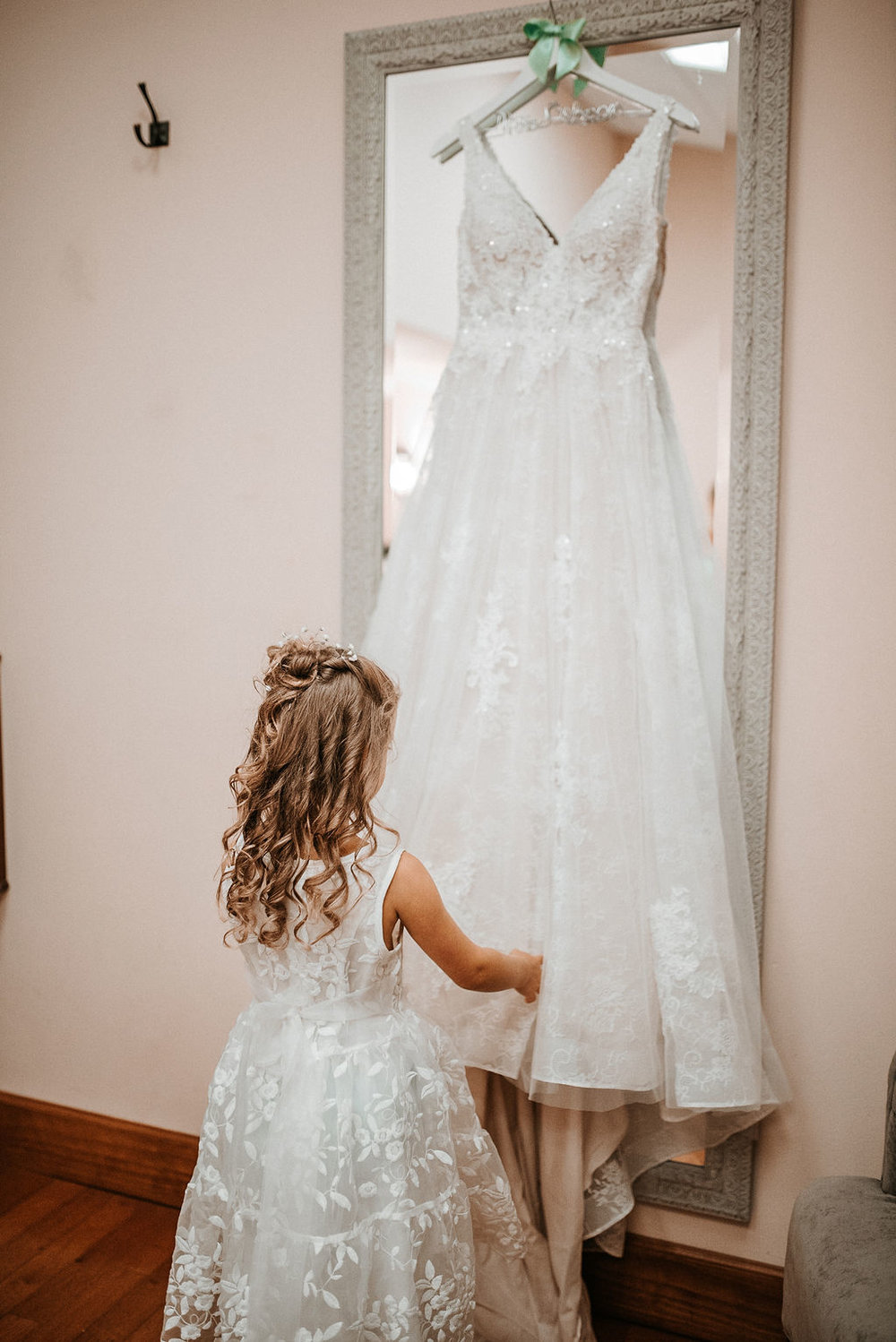 flower girl looking at bride's dress