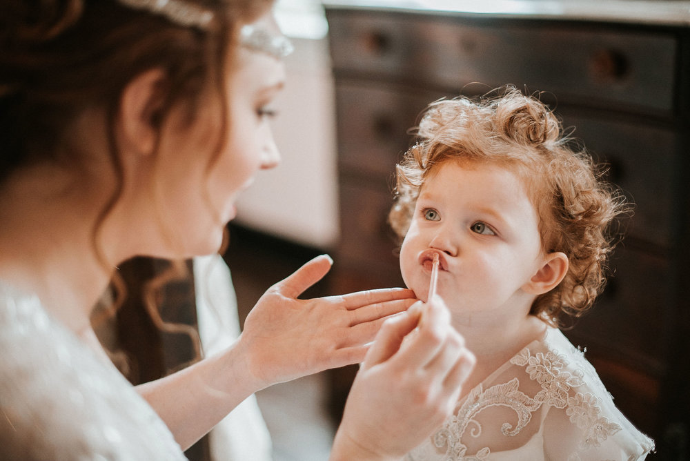 bride and her daughter putting on lip gloss