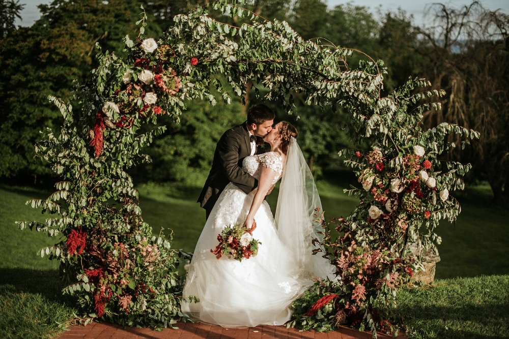 Bride and Groom kissing at the alter at Rosemont Manor