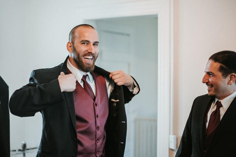 groom putting on jacket at Whitehall Estate