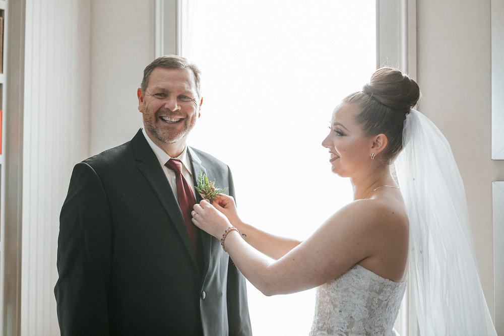 bride pinning boutonnière on father of the bride at Whitehall Estate