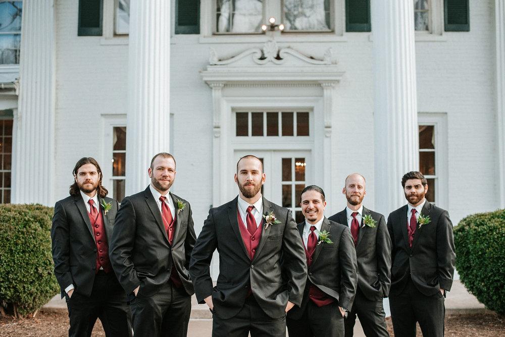 groom and groomsmen posing at Whitehall Estate