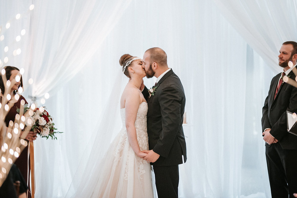 bride and groom kissing at the altar at Whitehall Estate
