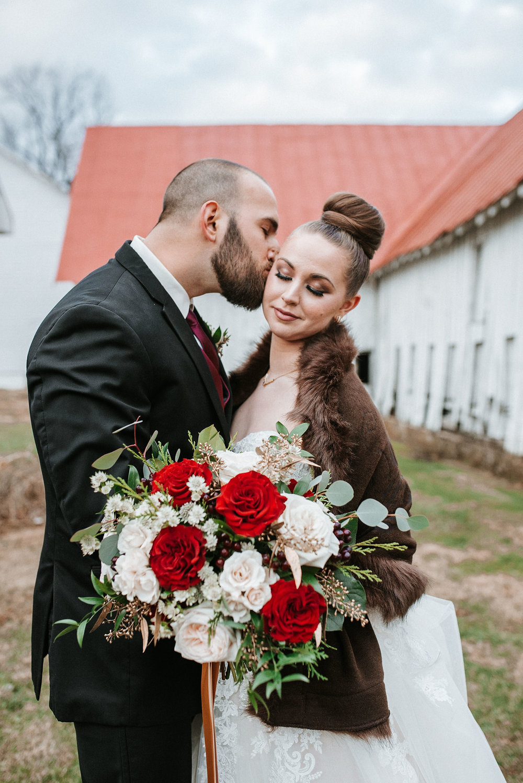 groom kissing bride on cheek at Whitehall Estate