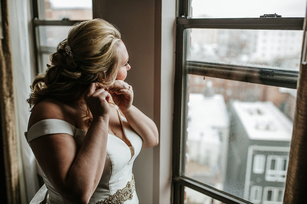 bride putting on earrings at the kimpton carlyle hotel