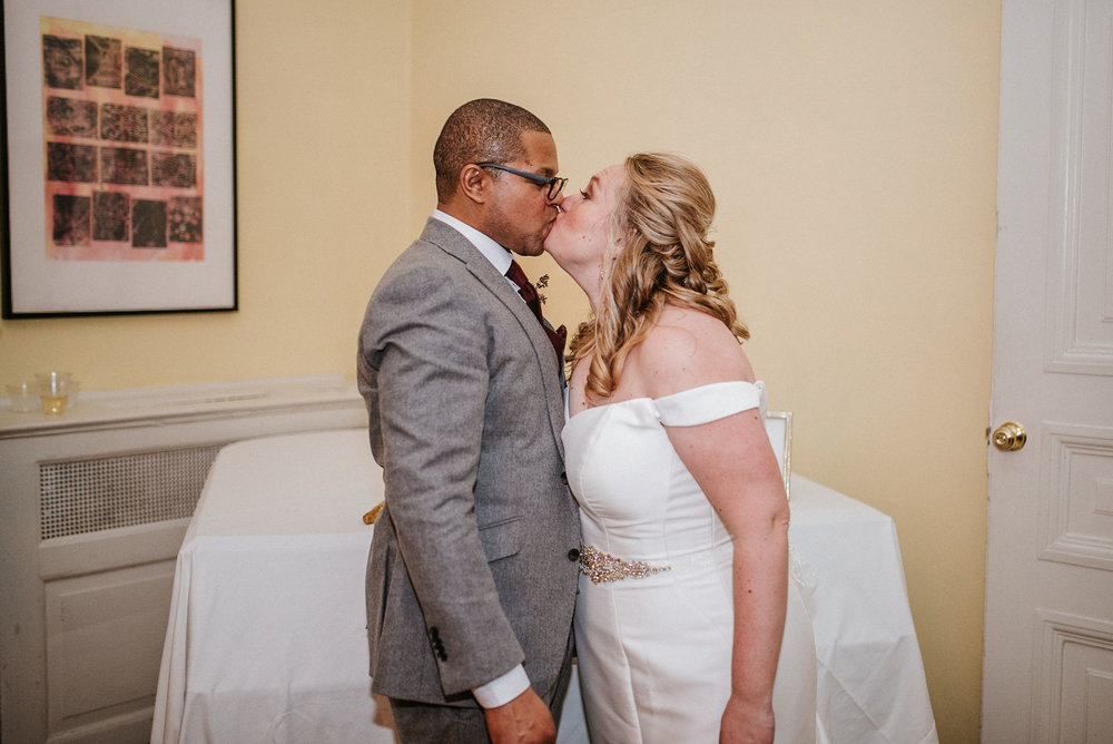 bride and groom kissing after cutting the cake at the josephine butler parks center