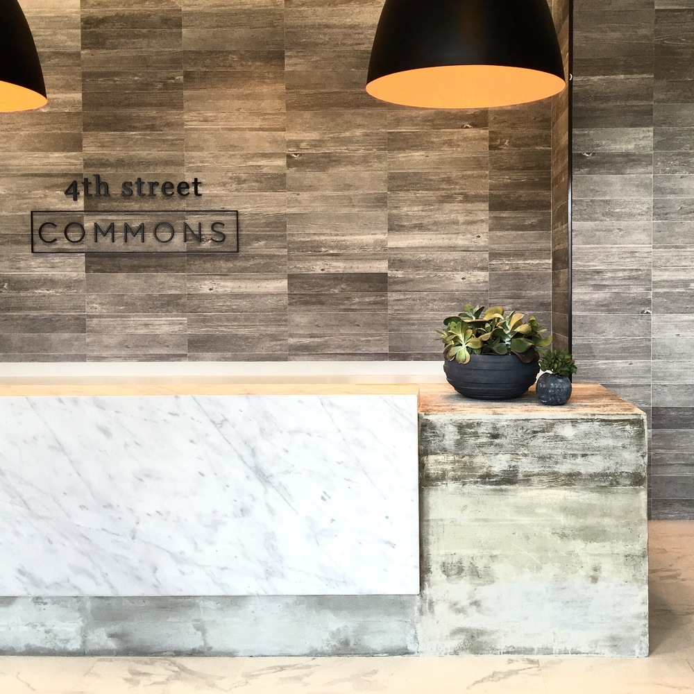A custom designed 20' reception desk made from cast concrete and Carrara marble waterfall skirt, sits under oversize bell pendants from Industry West. Bowls of succulents from Sprout are the perfect contrast in the texture heavy space.
