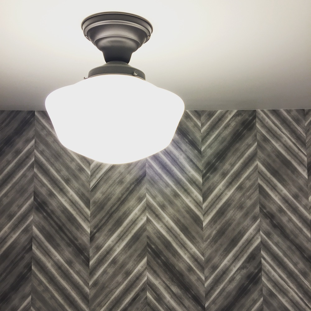Classic school house lights from Rejuvenation Lighting handsomely complements Wolf Gordon's Herringbone Etch wall covering.