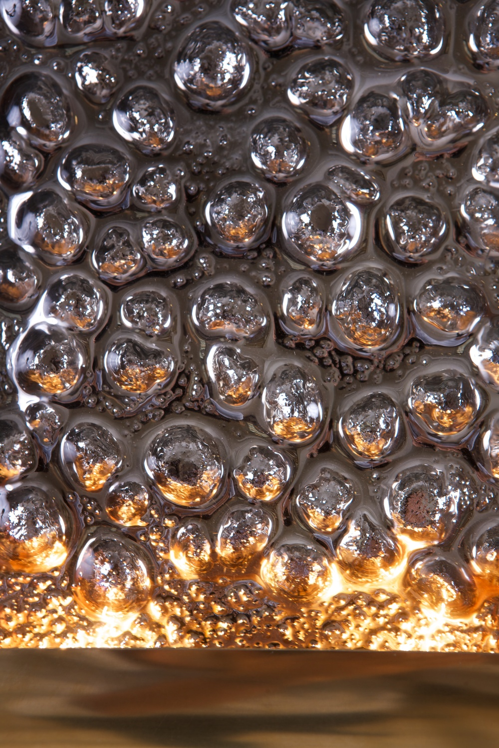 Detail of the mirrored glass of the Portal Sconce as lit by 2 halogen bulbs
