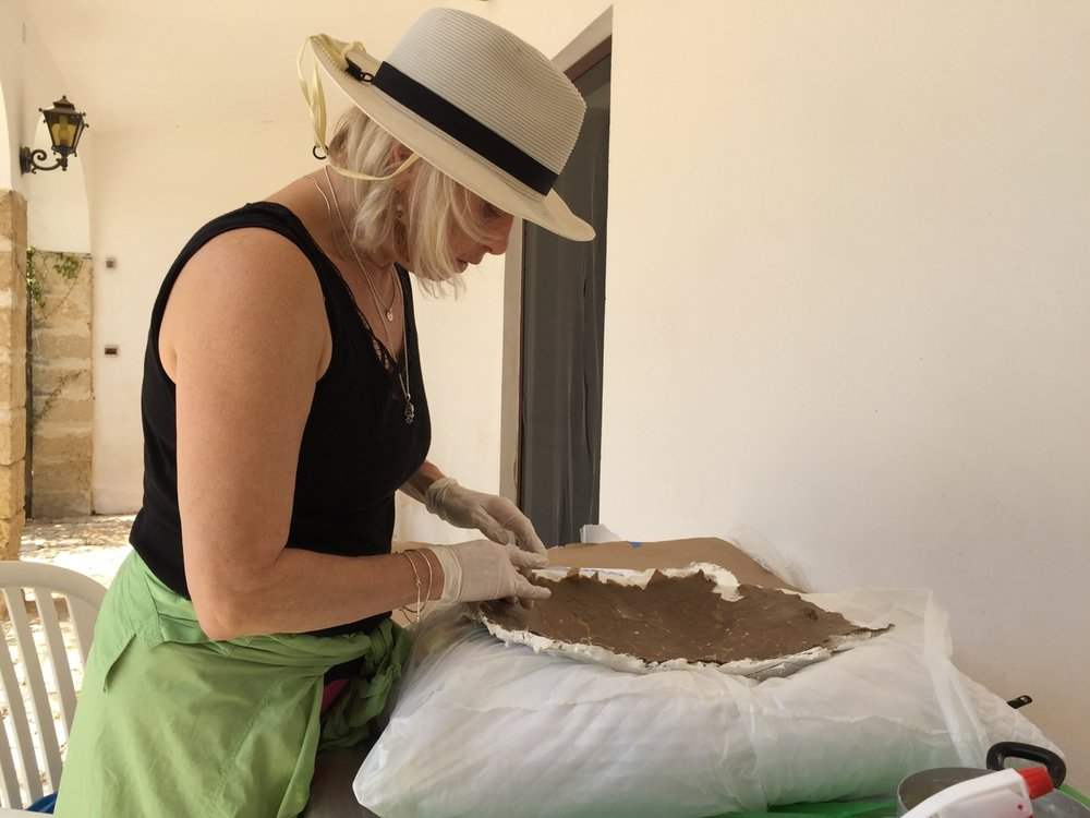 Artist Christine Palamidessi in  her summer studio in Puglia, Italy.  Shown here working in the arte povera technique of cartapesta..
