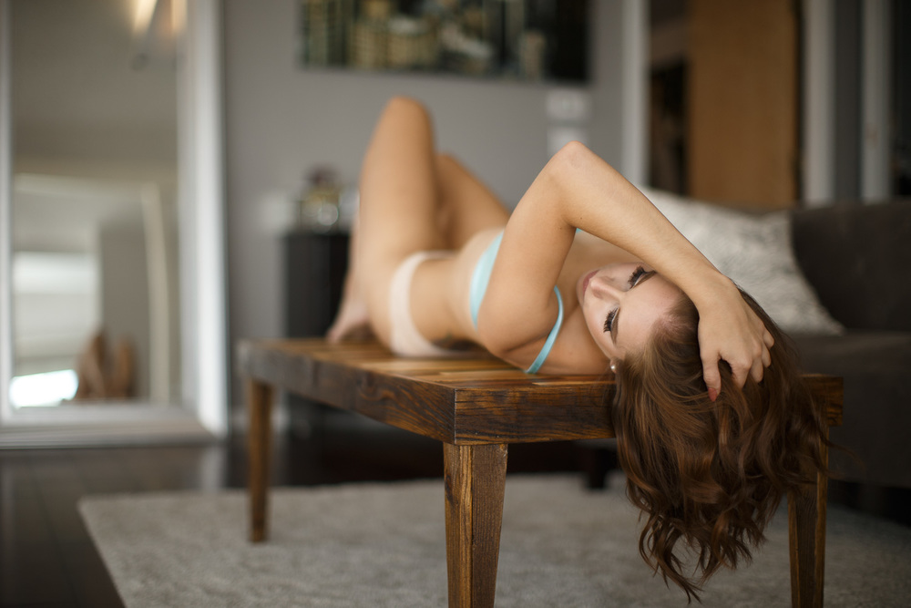 LA boudoir model laying on coffee table