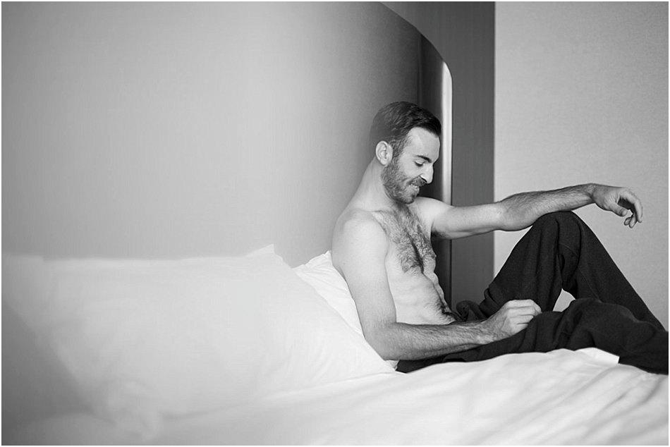man sitting on a bed shirtless wearing sweatpants