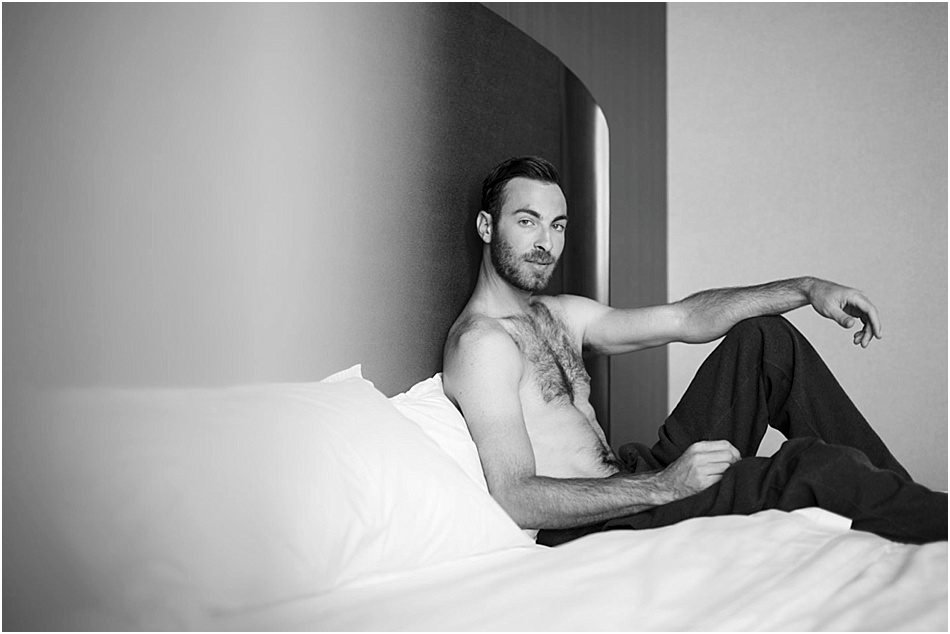 looking into the camera and shirtless a man sits on a bed