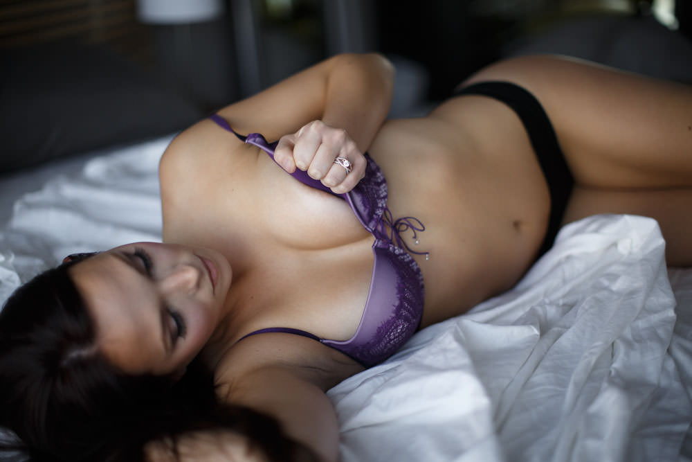 real woman during a boudoir shoot taking off her bra