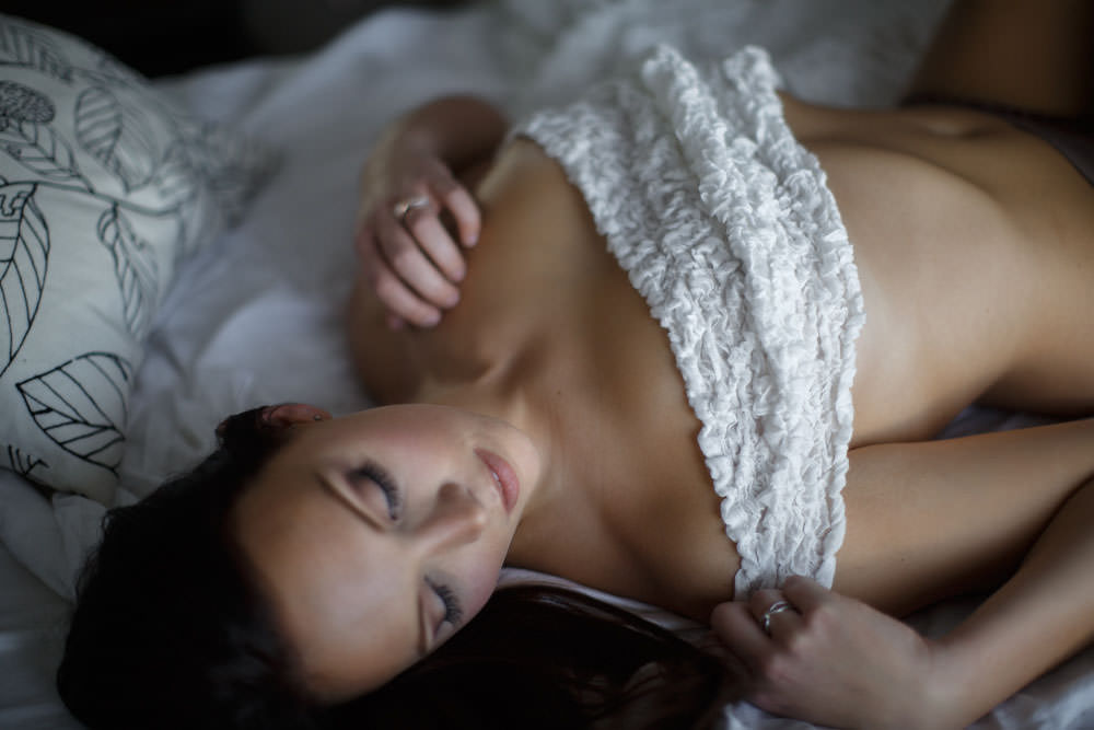 only a white sheet covers this womans breasts during her boudoir experience