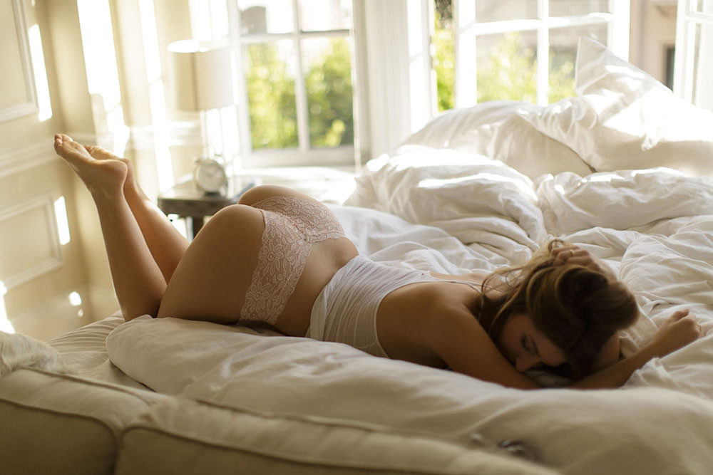 Model showcasing curves by laying on bed in Los Angeles during a Boudoir session