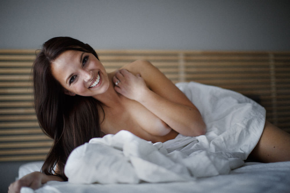 smiling boudoir portrait nude in white sheets on the bed