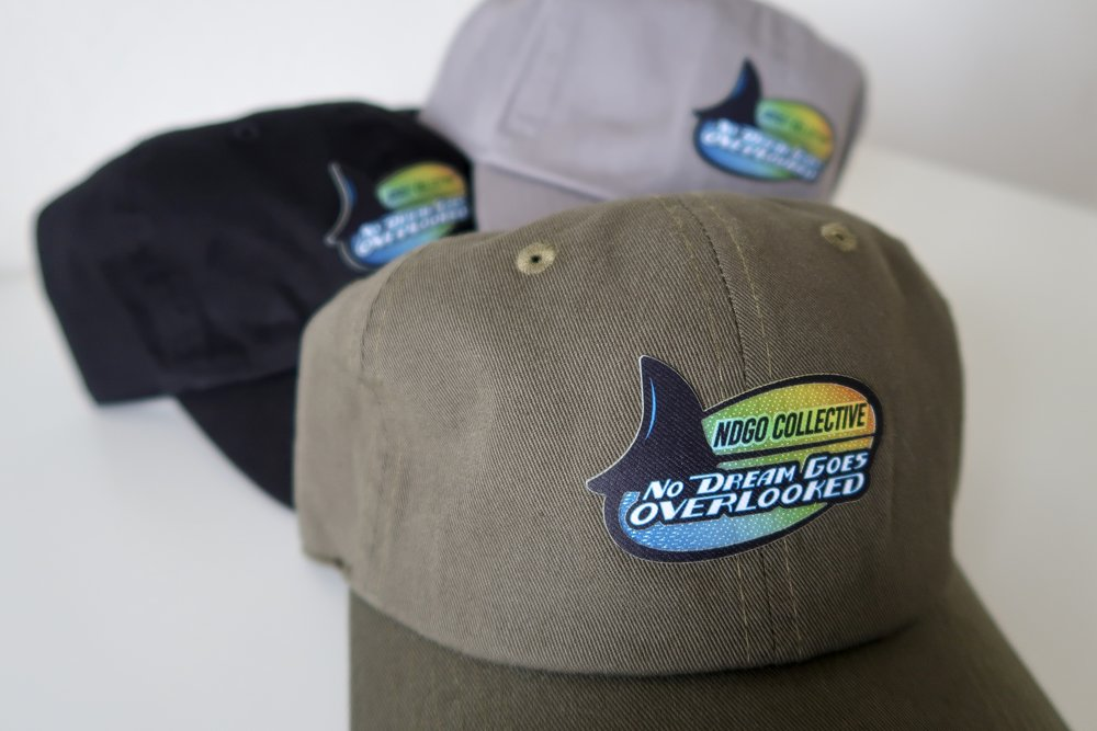 Now we're here.  With the success of the first dad hats, I decided to bring them back just in time for the start of summer.  No seriously, I remember when I first started this whole concept, I told myself that I'd never do the same design or same piece twice.  So many people wanted the last hats I had to release them four times!  Anyway, these patches are ridiculous, next level, something you need to see in person.  Pictures do not do them justice, and I'm not just saying this because they're my hats.  I've really never seen any patches like this.  Once they hit the sun or any light really, the gradient is iridescent. Plus the outlines of the letters are raised for that 3D feel.  You'll see.  No Dream Goes Overlooked. 5 Years this year.   - NDGO Jordan (@ndgojordan)