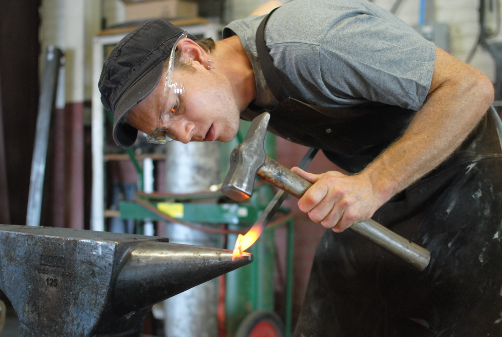 Blacksmith Kyle Lucia forging at the anvil