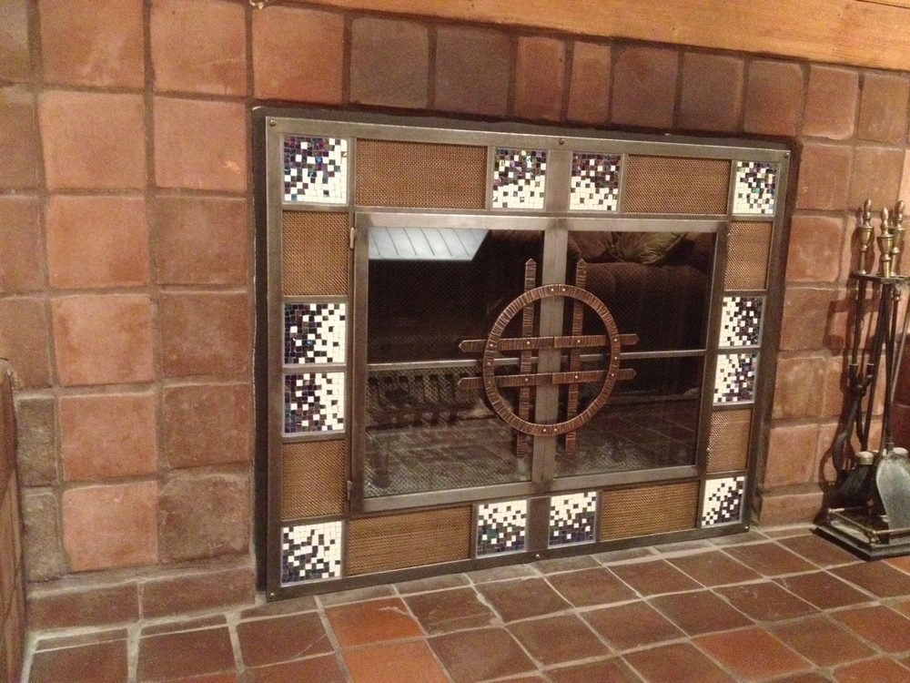 Custom firescreen with mosaic panels and forged bronze handles installed