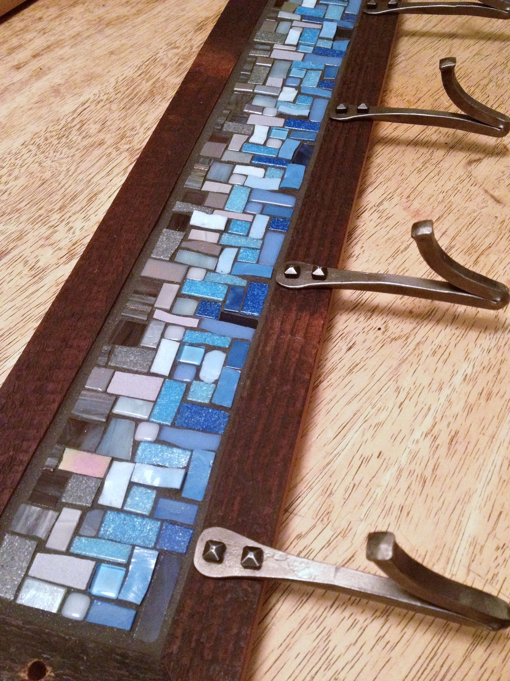 Blue and gray mosaic coat rack with modern hand forged V hooks in a reclaimed wood frame