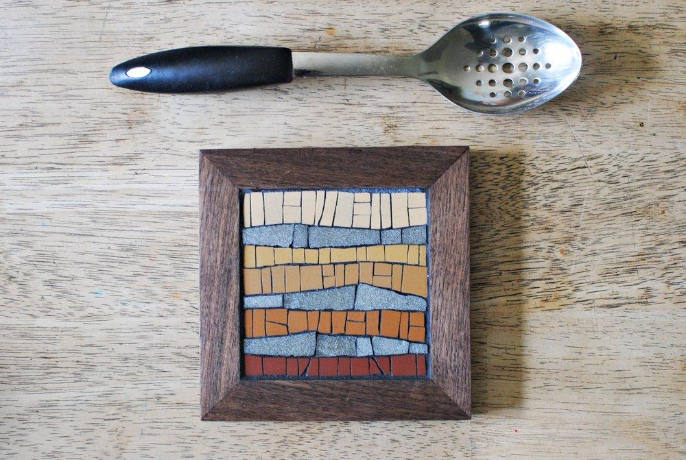Desert mosaic trivet on table
