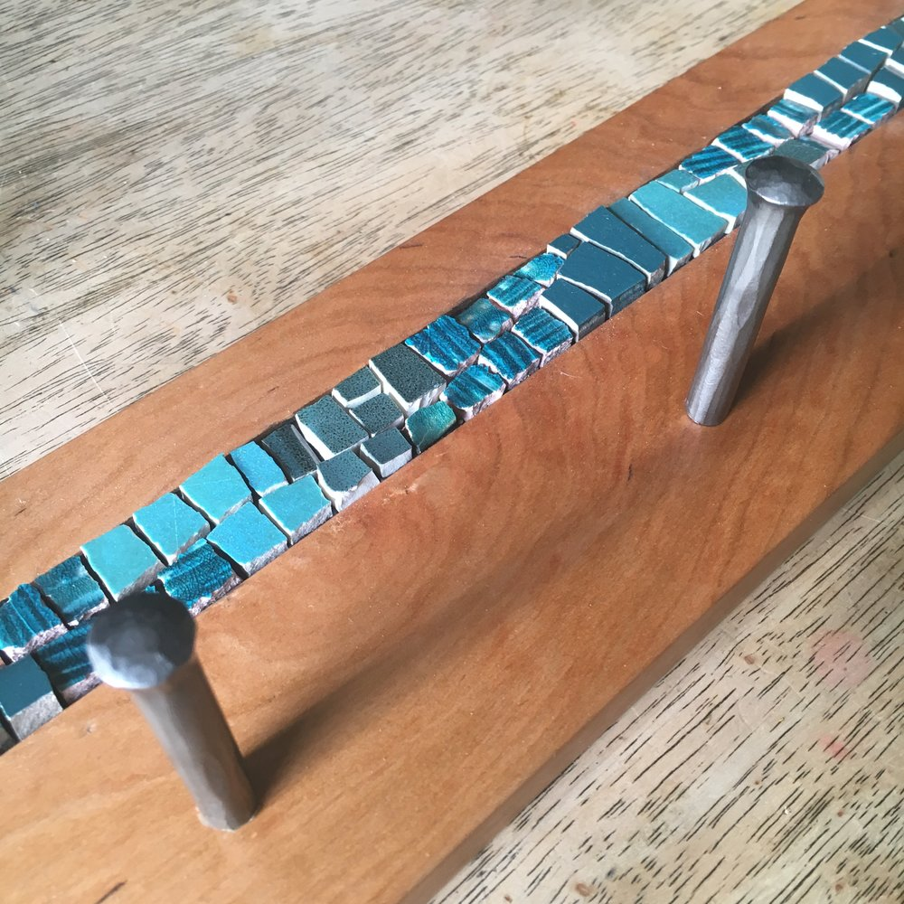 Teal mosaic coat rack with pegs detail