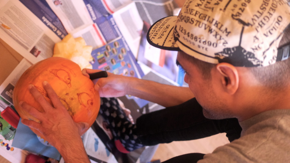Oscar designing his amazing pumpkin guy with the most personality i've seen on a gourd.