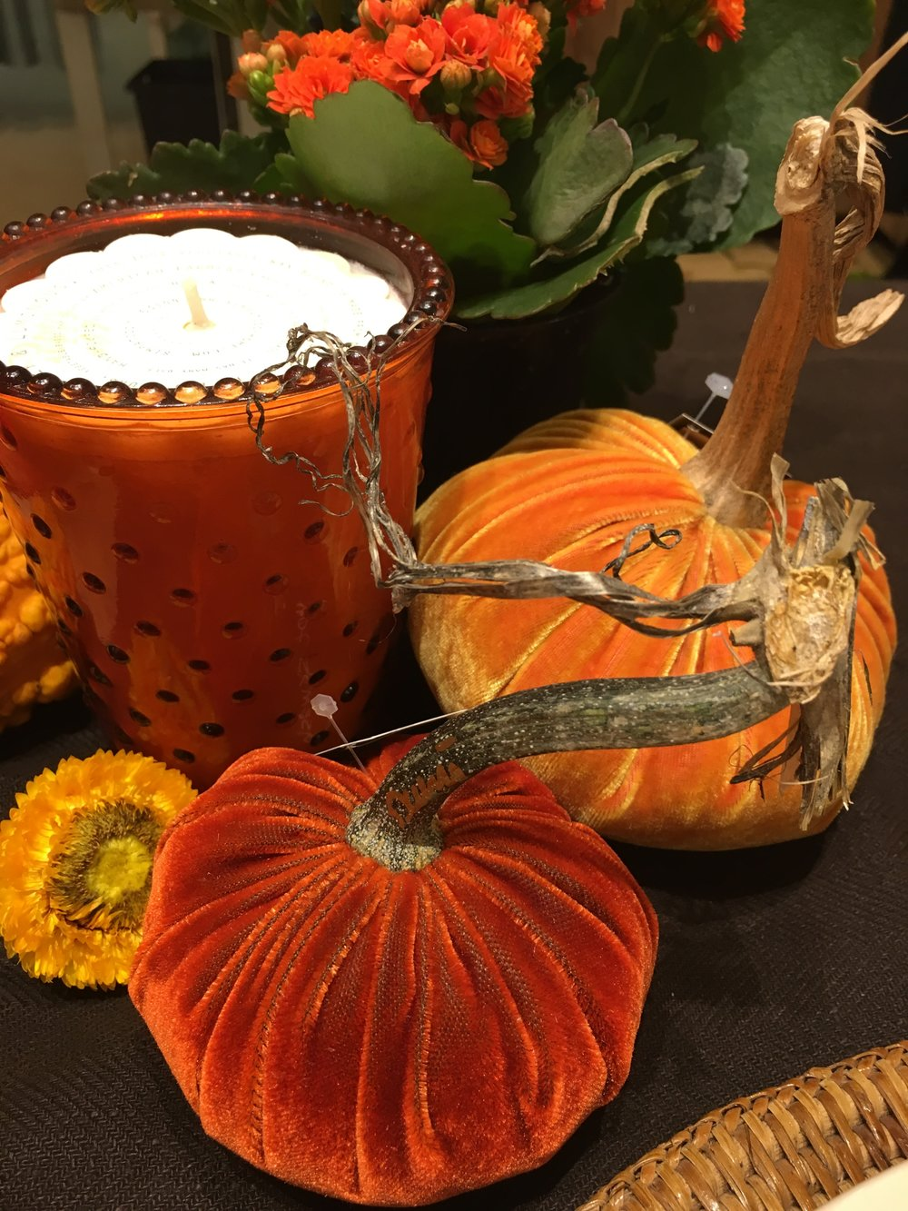 Holiday table decorations: candles, flowers and artificial gourds.