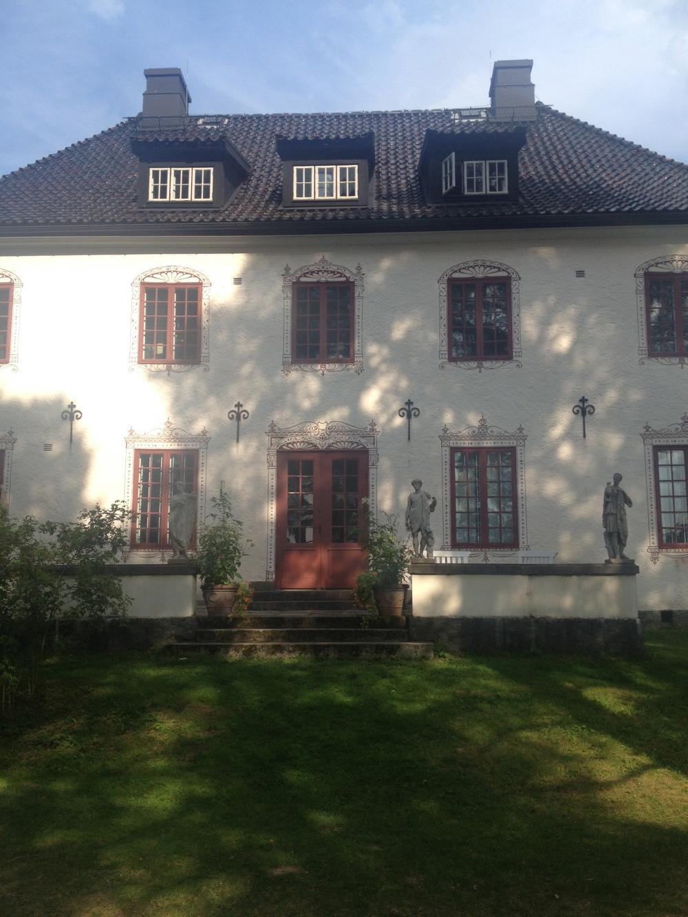 Husets baksida - lägg särskilt märke till de målade fönsterkarmarna   Foto:  Palatsliv