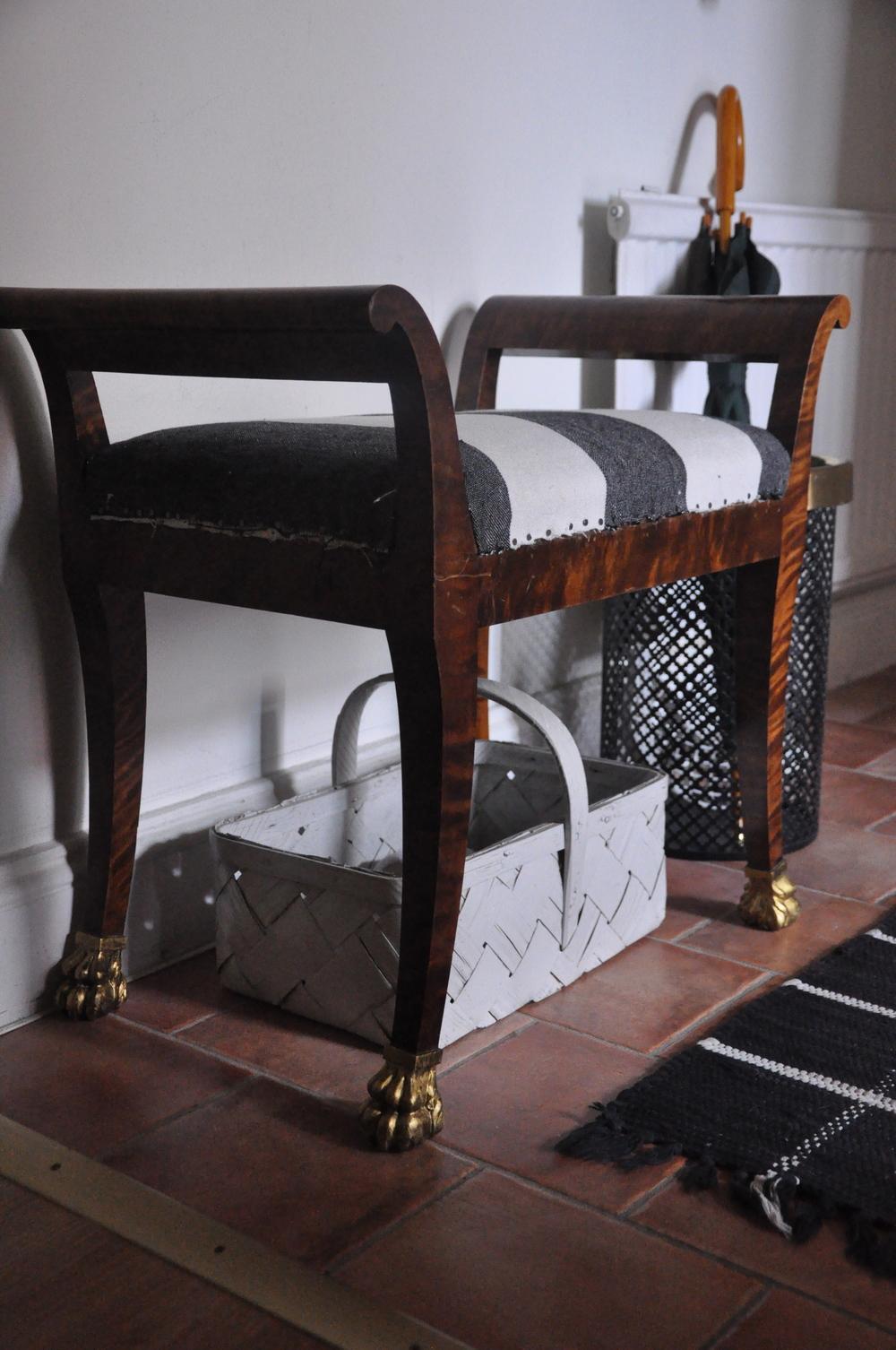 Pallen/taburetten, i ny svart/vit-randig klädsel från Designers Guilds och guldmålade fötter.     Foto:  Palatsliv