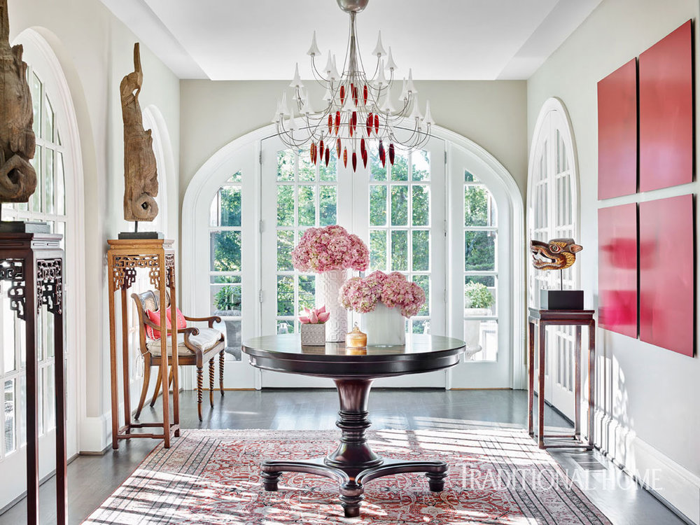 If you had told us that we would fall for a room with pink hydrangeas (well, that part would be true) mixed with red artwork and a red-patterned Persian rug, a modernist Baccarat crystal-and-wire chandelier and Asian artifacts, we might have been surprised at the suggestion, and yet, everything just falls together beautifully, each eclectic element playing off the other perfectly, with the light filtering in through the arched French doors adding to the enchantment.