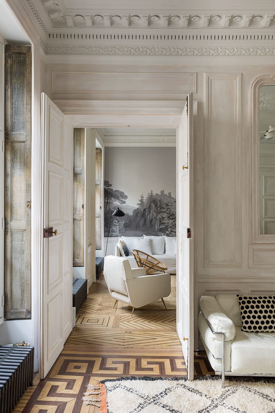The owner of this Paris apartment, Alice Razavi, lives in the United States and purchased the space to use as a vacation home for her family. French architect Alireza Razavi was called in to renovate the home, which is in disrepair, alongside decorator Sylvie Acker. The result is a striking mix of 1930's French armchairs intermingled with Moroccan rugs, sofas and chairs by Charlotte Perriand and Jean Prueve, geometric parquet flooring, grisaille wallpaper, and Serge Mouille chandeliers. The 230 square meter apartment, located in an 1830's building, had for many years belonged to the descendants of the poet Paul Valery.
