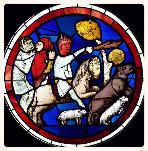 Medieval Stained glass depicting the devil driving on sinners. Musee De La Moyenne Age (Paris).