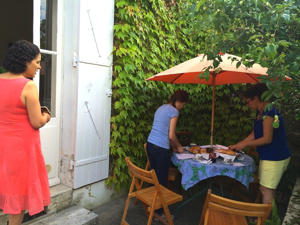 Bakhta (left), her daughter Tanya (middle) and Curry Leaf Cafe's operations manager Rachida Zitouni lay out the garden table ready for 'gouter' – a regional tradition that dictates you must eat something sweet with tea or coffee around 5pm every day