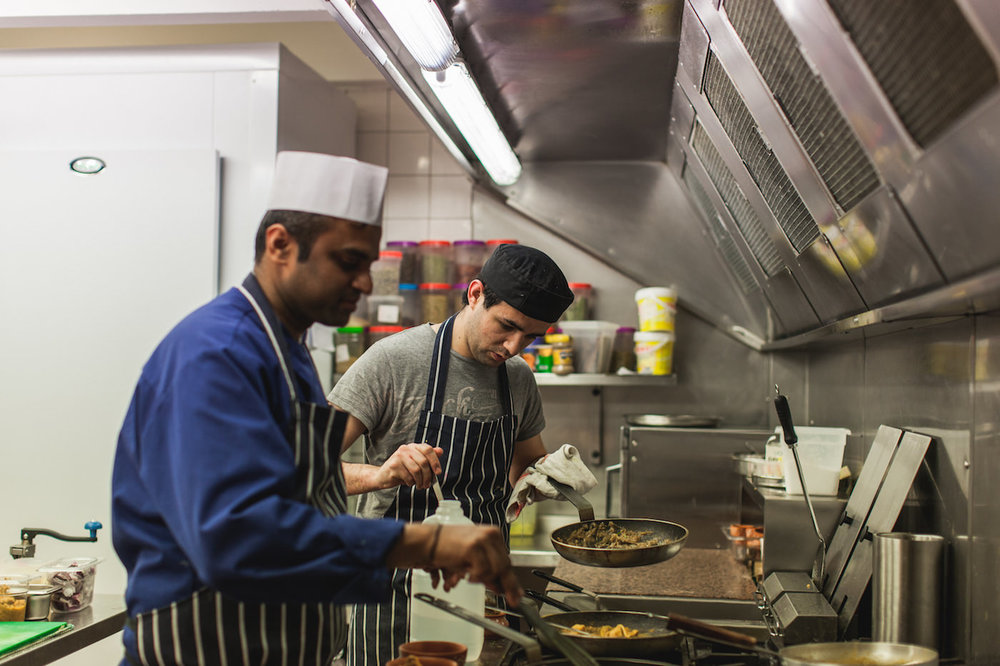 Damian (back of photo) training with chef Kanthi Thamma at the cafe in spring 2014, shortly after Curry Leaf Cafe was launched. Photo courtesy of Emma Gutteridge