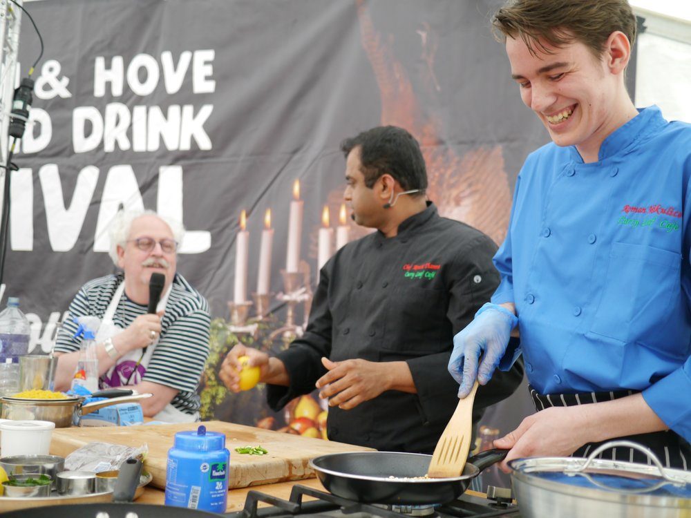 Chef Roman (far right) cooking with Curry Leaf Cafe co-owner Chef Kanthi Thamma (middle) and host Andrew Kay (left) at the Brighton Food Festival in August 2016