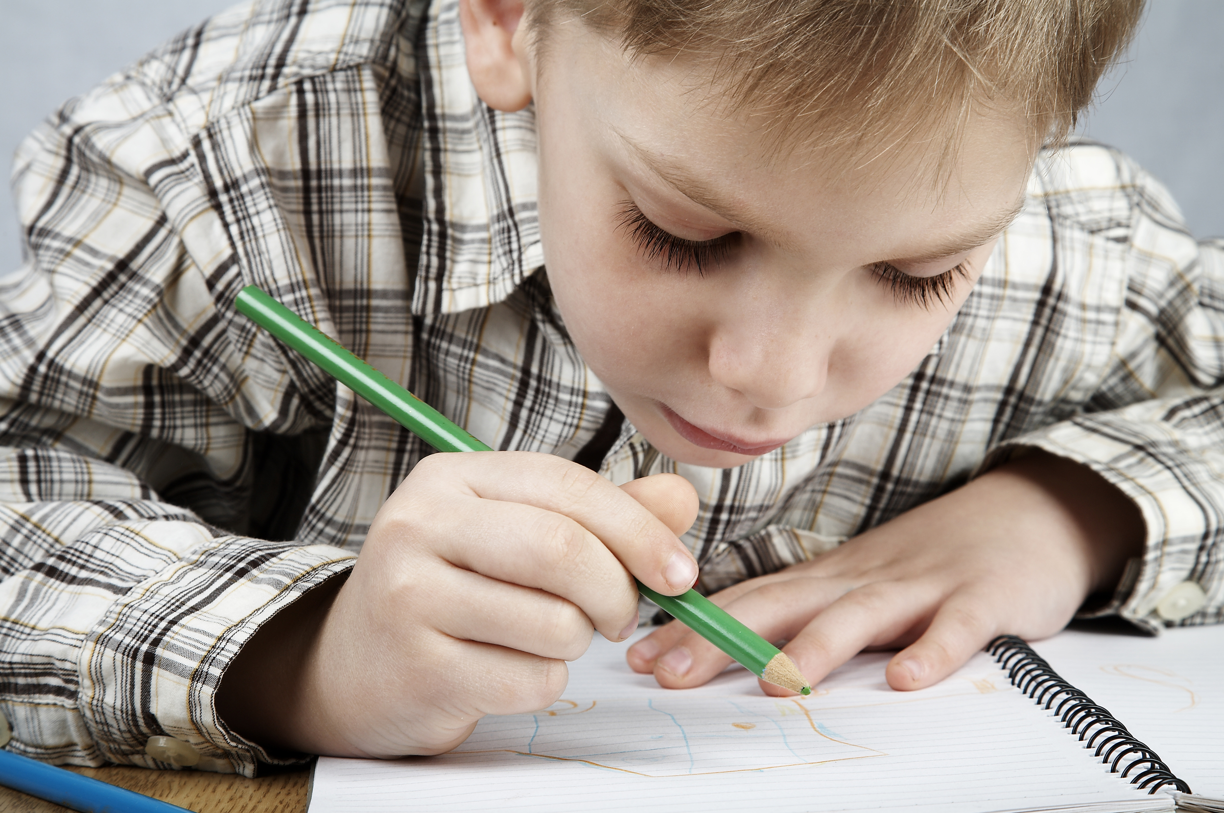 young boy writing with a pencil