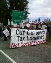 "Workers hold a sign saying ""Cut Corporate Tax Loopholes, not Social Services"""