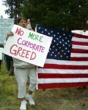 "Woman holding""no more corporate greed"" sign"