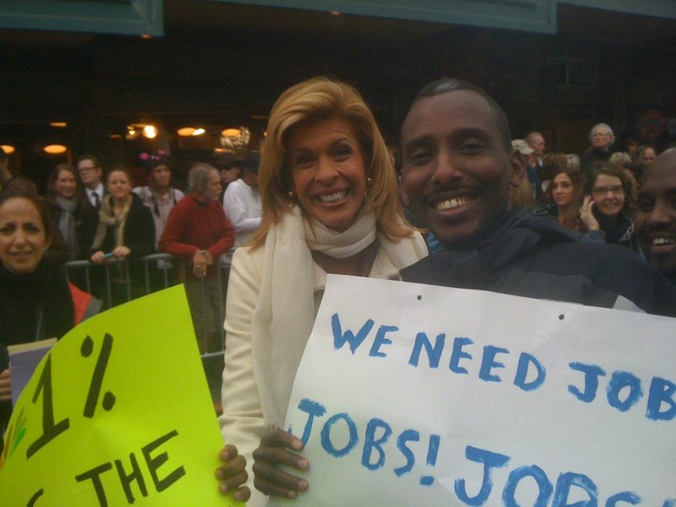 Hoda of The Today Show stands with a Working Washington member holding a jobs sign