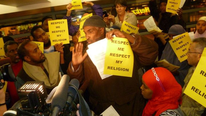 "Muslim Hertz employees holding signs ""Respect Me, Respect My Religion"""