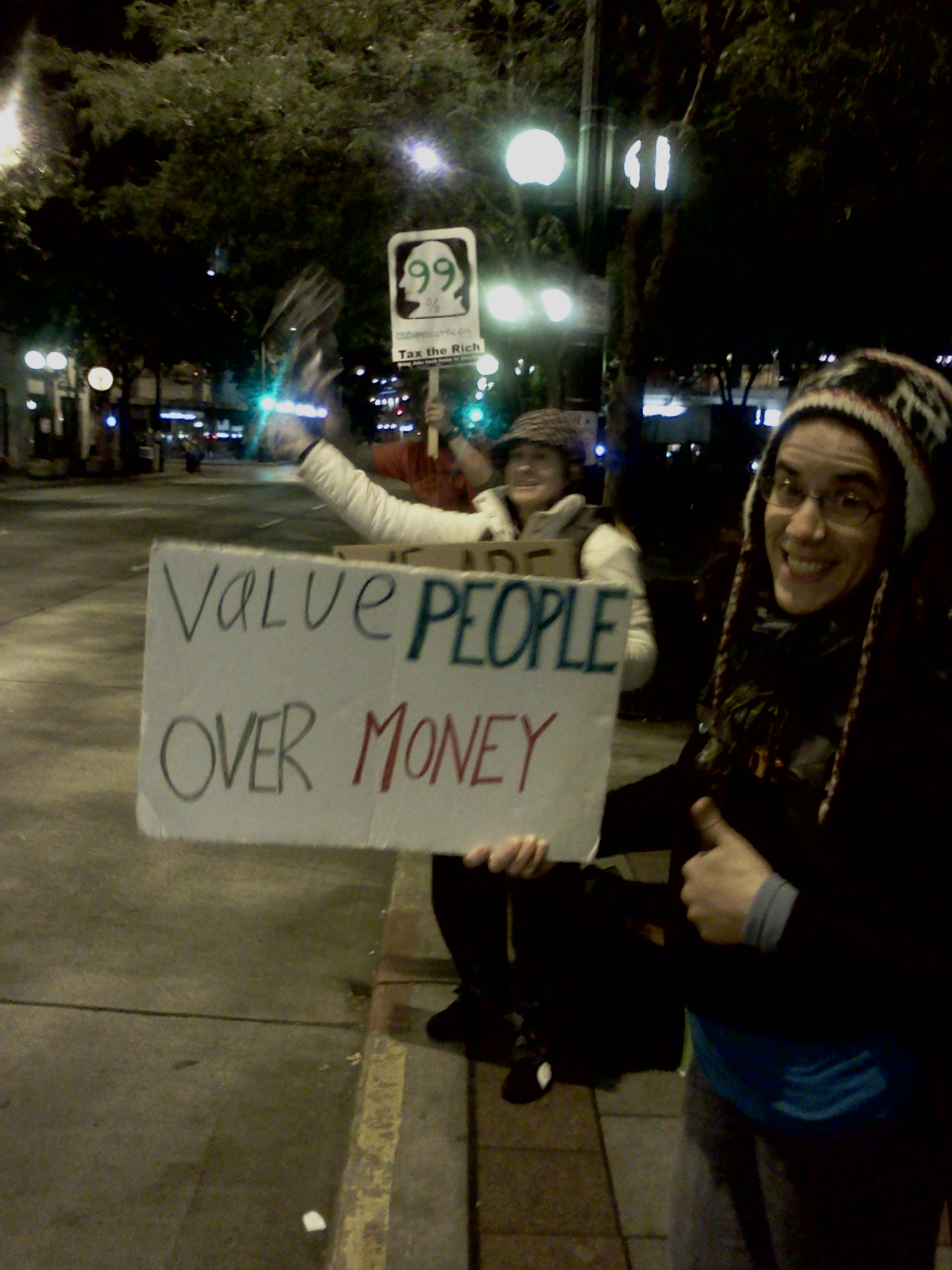 "Emma Klein holds up ""Value People Over Money"" sign at Occupy Seattle"