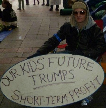 "Man holding ""Our Kids' Future Trumps Short-Term Profit"" at Occupy Seattle"