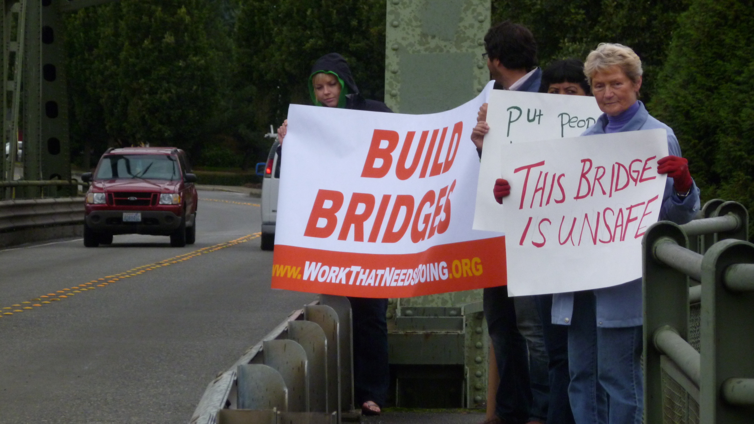 "Holding ""Build Bridges"" signs on an I-5 overpass"