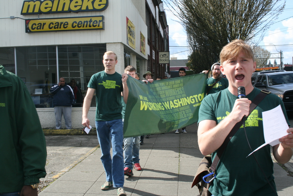 Luke Bridges, holding the Working Washington banner, spoke out why he is supporting $15 and workers' rights for Olympia.