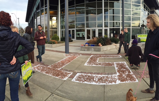 Workers spread 16,906 pennies onto a giant 15 to represent the 16,906 workers in Olympia who make less than $15/hr.