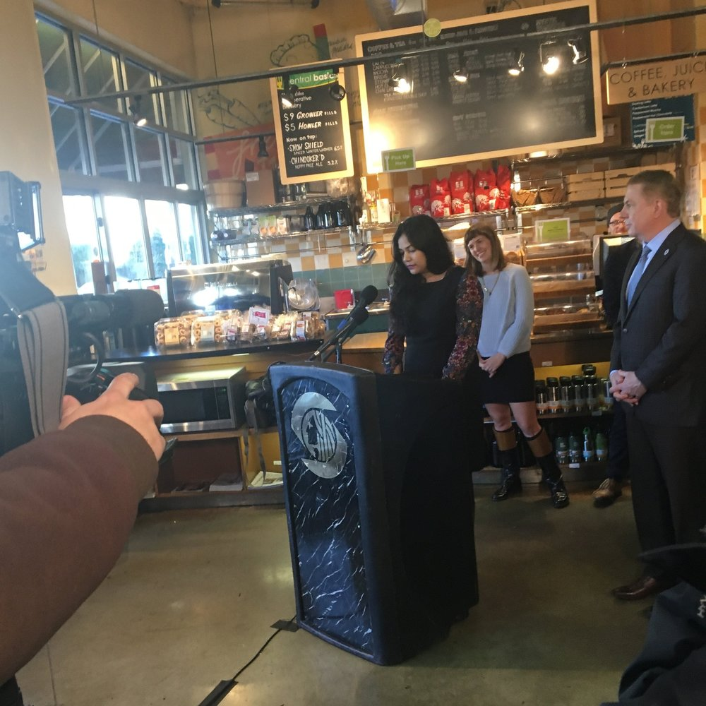 Sejal Parikh of Working Washington at the podium helping celebrate $15/hour at Central Co-op on Seattle's Capitol Hill. Also pictured: Nicole Grant of the Martin Luther King County Labor Council and Mayor Ed Murray, and a Central Co-op deli worker.