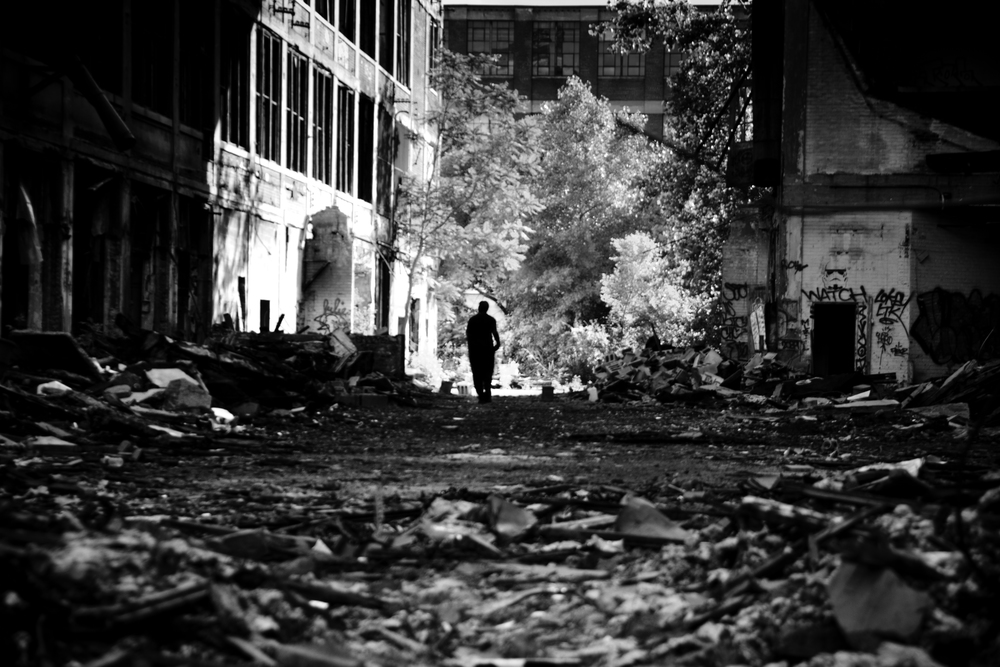 A scrapper wanders through the Packard Plant in hopes of finding what little metal may be left in the infrastructure. Packard Plant, Detroit.